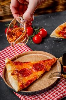 요리사는 페퍼로니 피자 조각에 매운 기름을 붓습니다. 고품질 사진