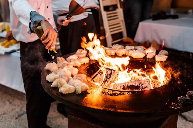 Шеф-повар наливает на гриль кусочки рыбного стейка с подсолнечным маслом.