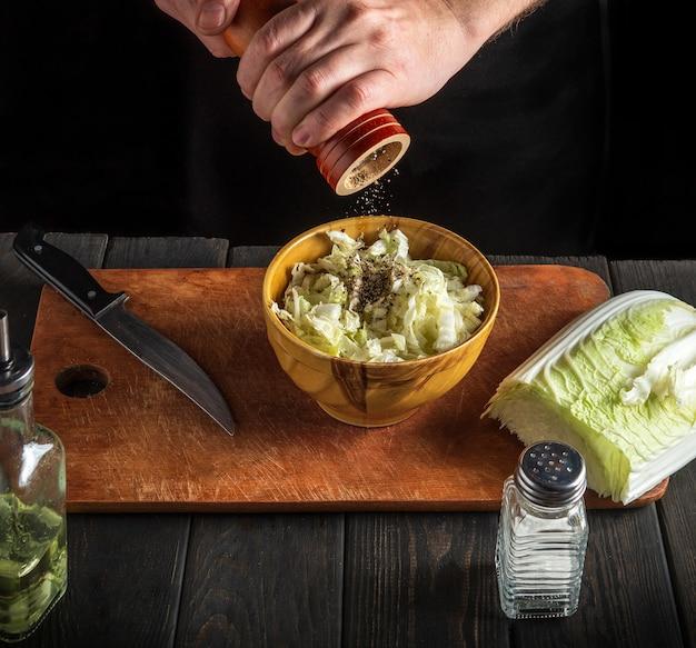 Шеф-повар готовит салат из напы. крупным планом повар, добавляющий перец в салат с помощью ручной мельницы. вид сверху