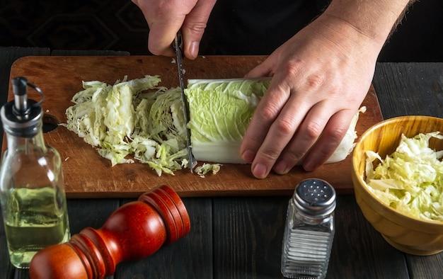 Шеф-повар готовит салат из капусты напа. крупный план шеф-повара режет капусту ножом на разделочной доске