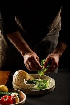 シェフがシーフードと野菜のサラダを用意します