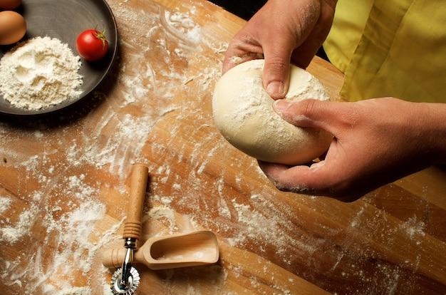 シェフはフェットチーニ、スープ、ピザの生地を準備します