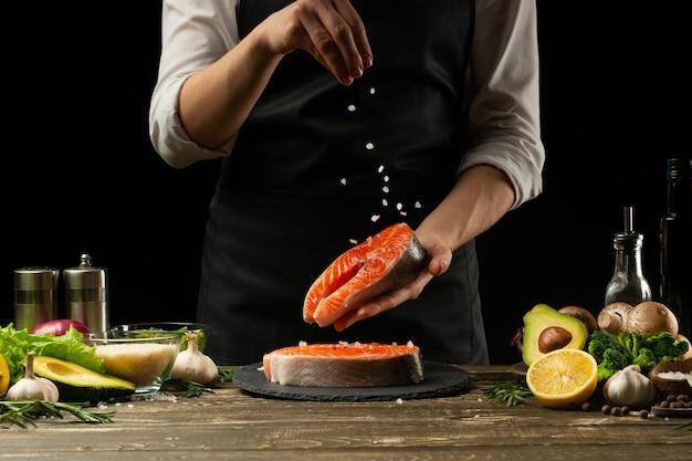 요리사는 신선한 연어 생선, smorgu 송어, 재료로 소금을 뿌리는 것을 준비합니다.