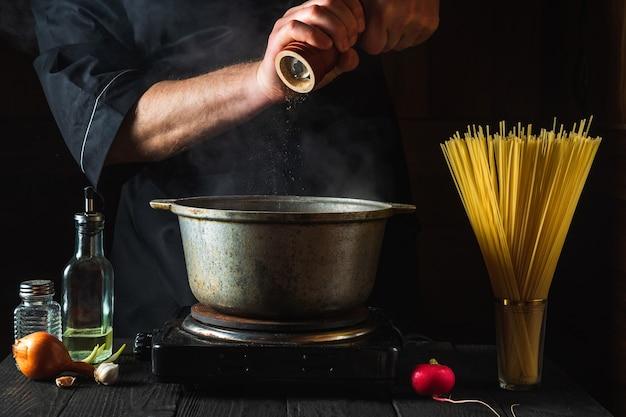 요리사는 야채를 배경으로 이탈리아 파스타를 준비합니다.