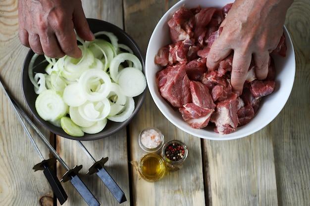 シェフがバーベキュー用の肉を準備しますボウルに肉片を入れます