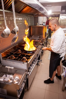 シェフはレストランのキッチンで直火でストーブの上で料理を準備します。