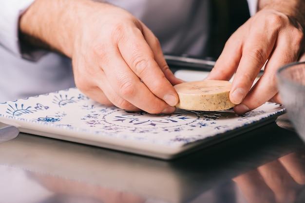 Повар кладет на тарелку кусок фуа-гра.