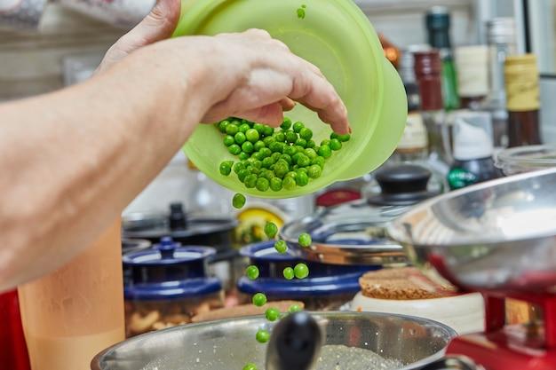 요리사는 그릇에 완두콩을 넣어 아스파라거스와 완두콩으로 구운 음식을 만듭니다. 단계별 조리법.