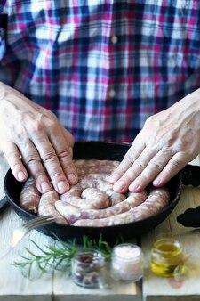 Шеф-повар кладет на сковороду сырые сосиски