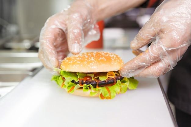 シェフの手が完成したバーガーを示しています。レストランでハンバーガーを準備しています。衛生要件に基づいた使い捨て手袋をした調理人の手。