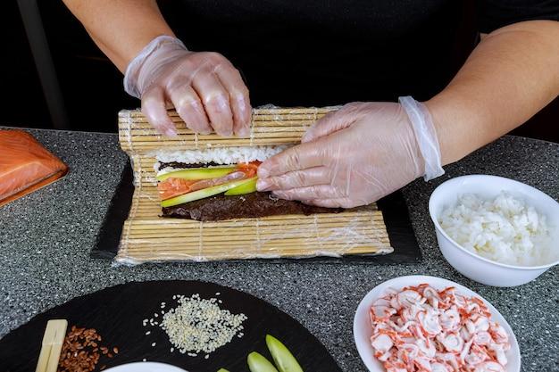 요리사의 손이 연어로 일본 스시 롤을 만듭니다.