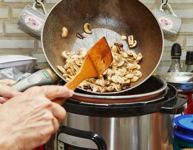 Шеф-повар бросает грибы со сковороды в скороварку, чтобы приготовить блюдо.