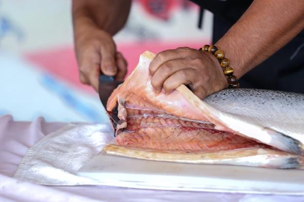 요리사가 생선, 연어 생선을 돌리고 있습니다.