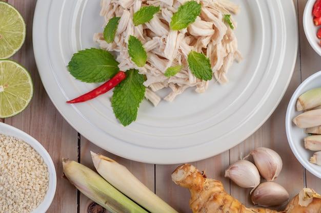 Курица, которая граничит, готовится и помещается в белую тарелку вместе с листьями мяты.