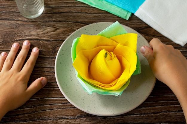 아이가 냅킨에서 꽃을 더합니다. 축제 테이블 세팅 핸드메이드