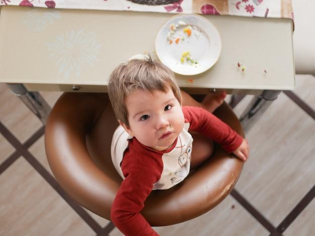 テーブルにいる子供は上面図を食べます。幼年期、食糧および人々のコンセプト-レストランやカフェで夕食に健康的な朝食を食べる小さな子供