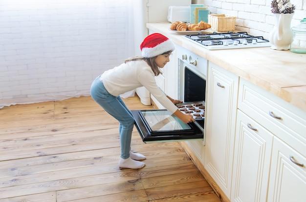 Ребенок печет и пробует рождественское печенье