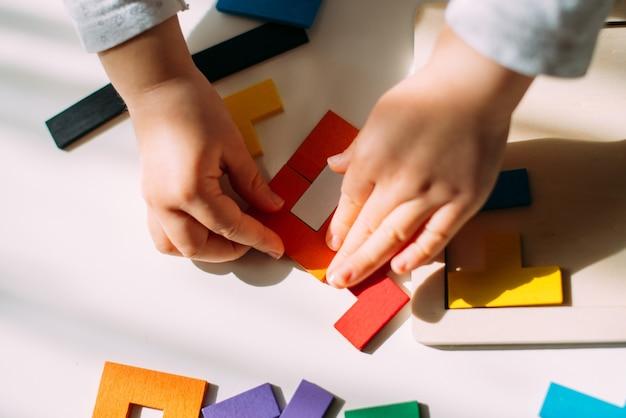 Ребенок создает фигурку из цветной головоломки на столе.