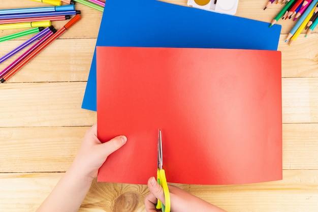 Ребенок режет цветную бумагу ножницами и множеством карандашей и красок для рисования