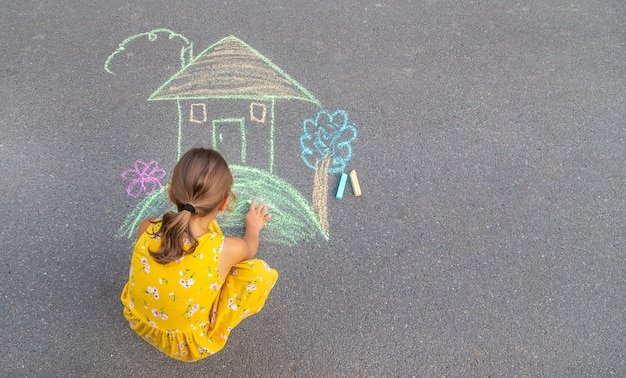 Ребенок рисует домик на асфальте. выборочный фокус.