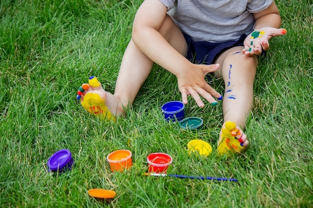 Ребенок рисует узор на ножке. забавный рисунок с яркими красками на теле. выборочный фокус