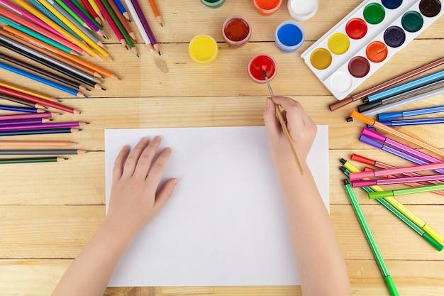 Ребенок рисует и много карандашей и красок для рисования на деревянном столе