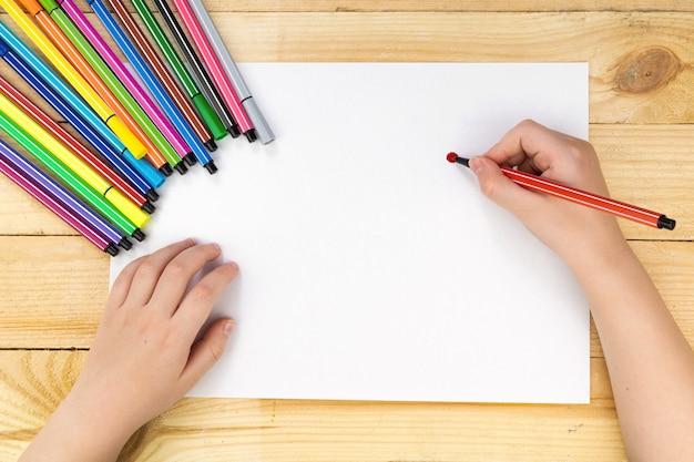 Ребенок рисует и много карандашей и красок для рисования