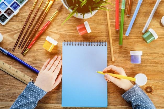 子供は、木製のテーブルにフェルトペンと絵の具でノートを描きます。