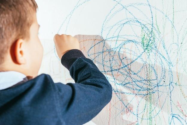 子供は色のついたチョークで壁に描きます。少年は家で創造性に取り組んでいます