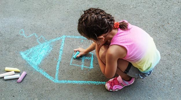 子供はアスファルトにチョークで家を描きます。セレクティブフォーカス。描く。
