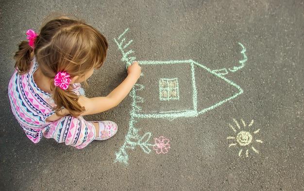 Ребенок рисует дом мелом на асфальте. выборочный фокус.