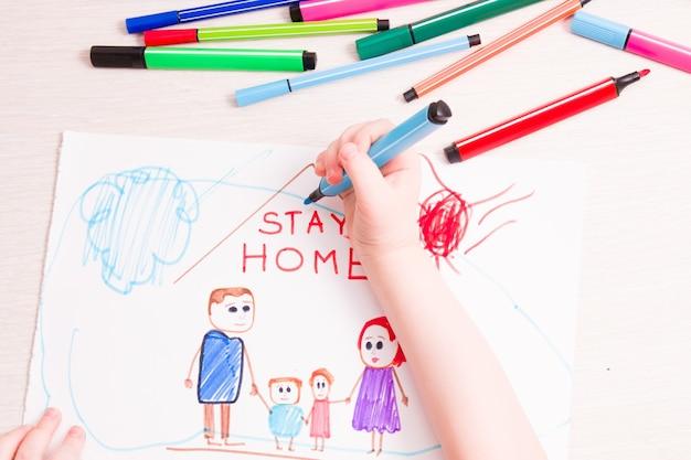 Ребенок рисует фломастерами концепцию семьи и домика на бумаге.
