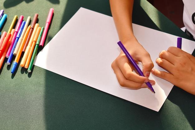 아이는 종이에 펠트 펜으로 그림을 그립니다. 유치원에서 아이들의 발달.