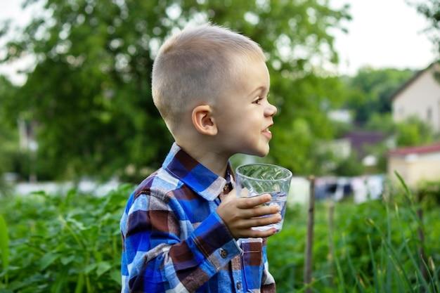 Ребенок пьет чистую воду на природе. выборочный фокус
