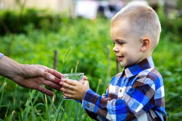 Ребенок пьет чистую воду на природе.
