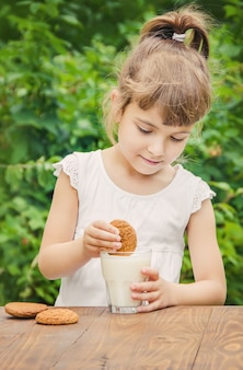 子供は牛乳とクッキーを飲みます。セレクティブフォーカス