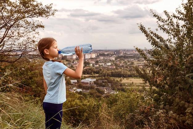 Ребенок пьет воду из бутылки во время путешествия.