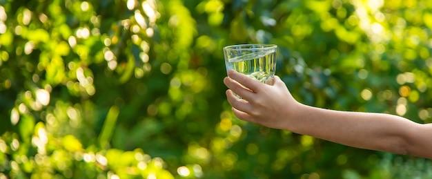 아이는 유리에서 물을 마신다. 선택적 초점입니다. 어린이.