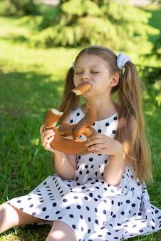 아이는 신선한 공기를 마시며 즐겁게 빵을 먹습니다.