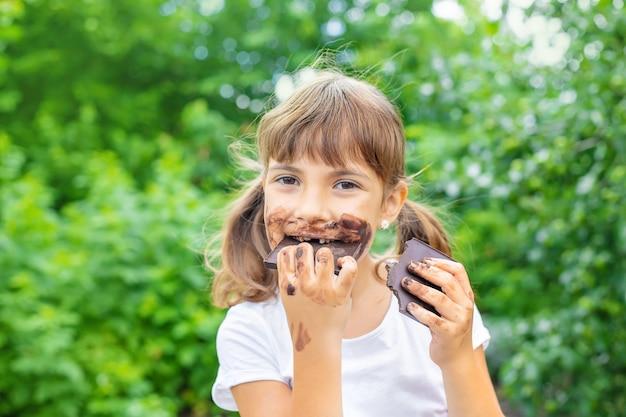 아이는 초콜릿 바를 먹습니다.
