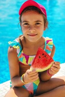 子供はプールの近くでスイカを食べます。セレクティブフォーカス。子供。