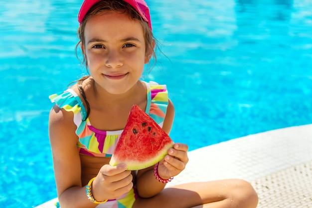 子供はプールの近くでスイカを食べます。セレクティブフォーカス。