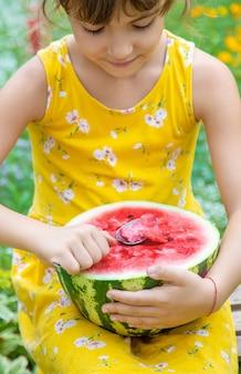 Ребенок ест арбуз ложкой