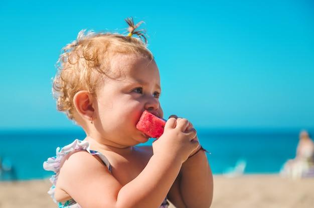 子供は海で果物を食べる。セレクティブフォーカス。子供。