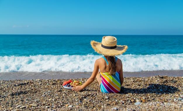 子供は海で果物を食べる。セレクティブフォーカス。