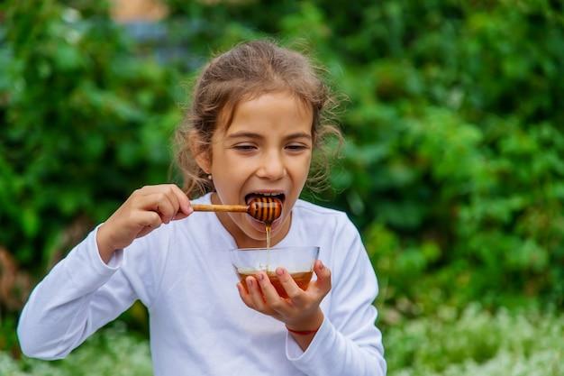 子供は蜂蜜とリンゴを食べます。セレクティブフォーカス。