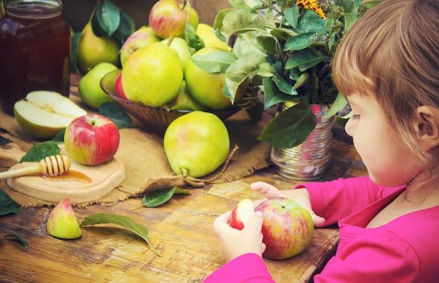 Ребенок ест мед и яблоки. выборочный фокус.