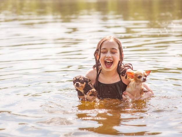 아이는 개와의 관계를 즐깁니다. 두 마리의 치와와를 안고 있는 소녀가 강에서 헤엄치고 있습니다.