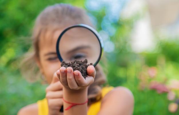 子供は虫眼鏡で地面を調べます。セレクティブフォーカス。自然。