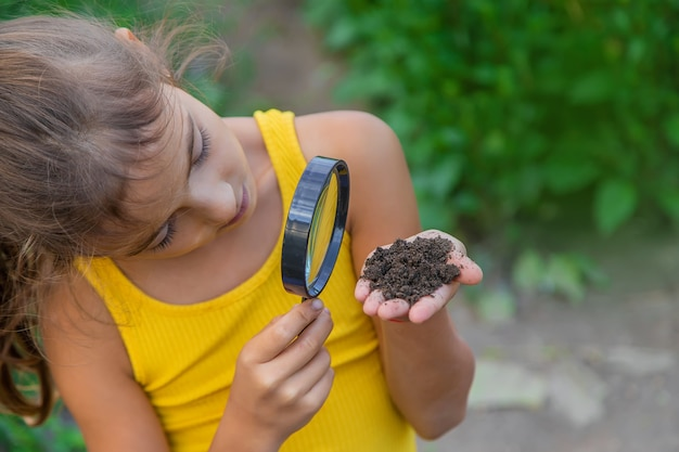 子供は虫眼鏡で地面を調べます。セレクティブフォーカス。